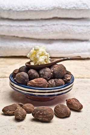 mantequilla: Las nueces de karité en un plato con una cuchara de madera de la manteca de karité Foto de archivo
