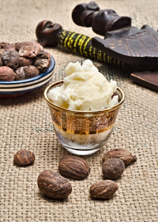Still life with shea butter in a glass and shea nuts with african objects in the background