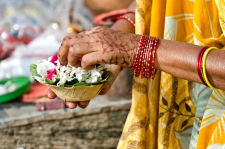 A woman set the candle and the flowers for the morning rituals to Ganges Stock Photo