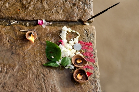 Candle, flower, incense and red powder offered to the river Ganges photo