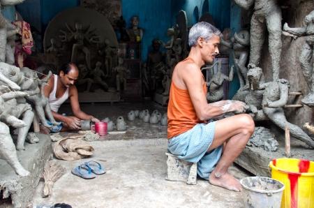 calcutta: Kolkata, India-August 2012: two craftsmen working on Durga statues in Kumartouli. Kumartouli is a traditionally potters' quarter in northern Kolkata Editorial