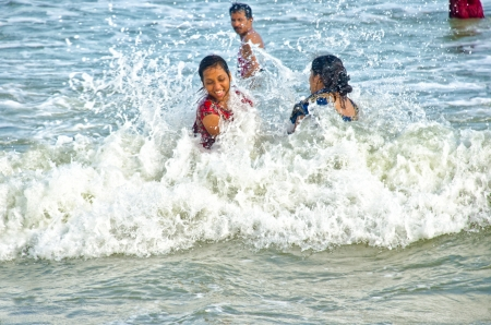 puri: Puri, India-August 15, 2012: two unidentified girls take a bath on the beach of Puri. Puri is in the state of Orissa, on the shore of the Bay of Bengal. It is known for being a tourist attraction and a Hindu sacred place. Editorial