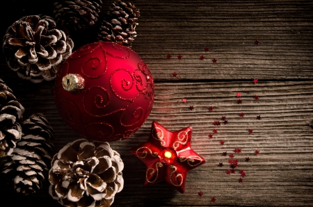 Red Christmas ball and candle with pine cones on wooden top photo