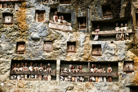 sulawesi: Traditional Tau tau, wooden statues representing dead men in a rock wall near Lemo, Sulawesi, Indonesia Stock Photo