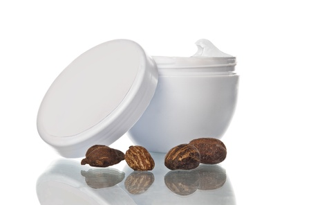 shea butter: shea butter in a pot and nuts, white background and reflection Stock Photo