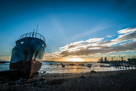 Abandoned and ruined ship in the harbor of Makassar, Indonesia at sunset