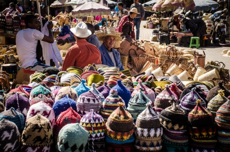 crocket: Marrakech, Morocco - March 19, 2013: people in a traditional street market located in the hearth of the the Medina of Marrakesh in Morocco, selling wool hats.
