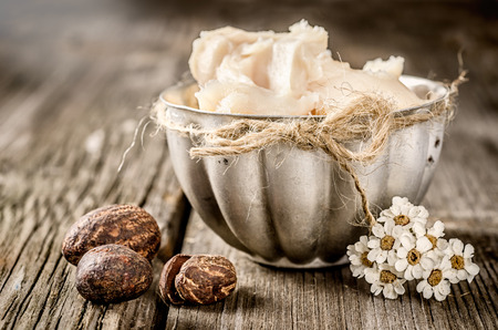 cosmetic cream: Shea butter and nuts on a wood