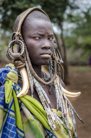 MAGO NATIONAL PARK, ETHIOPIA - August 10  unidentified woman from Mursi Tribe on August 10 2014  Mursi wear many ornaments made by natural materials, like elephant teeth