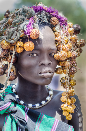 JINKA, ETHIOPIA - 10 August: unidentified beautiful girl from Mursi tribe in Mago National Park, Jinka, on 10 august 2014. Mursi people usully paint their bodies and use many natural ornaments like leaves and fruits