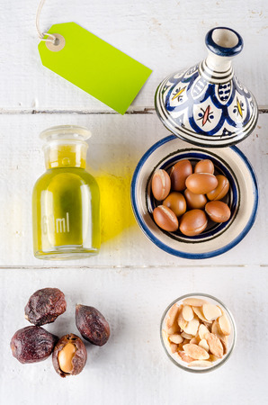 anti ageing: Argan fruits in different conditions (shell, nut and almond) with argan oil in a glass bottle. Added a label for copy space. A little Moroccan tajine contain the fruits