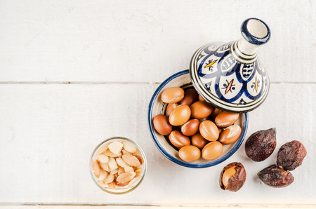 anti ageing: Argan Fruit on a wooden tabletop, Some fruit are without shell, other are in a Moroccan Tajine