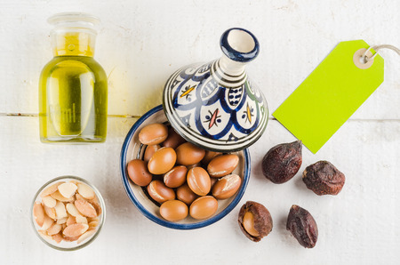 Argan Fruit on a wooden tabletop, Some fruit are without shell, other are in a Moroccan Tajine Stock Photo - 33255282