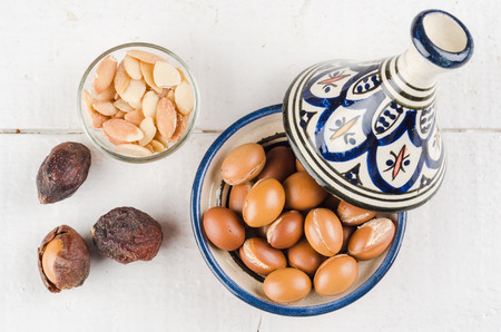 Argan Fruit on a wooden tabletop, Some fruit are without shell, other are in a Moroccan Tajine