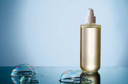 cleanser: Beautiful bottle of liquid cleanser with soap bubble on a reflective surface.