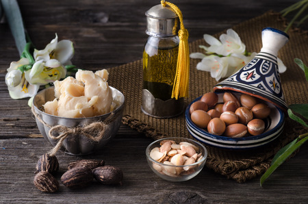 Still life of Argan oil and fruit and shea butter with nuts on a wooden table with flowers