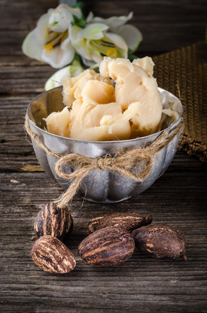 A cup full with shea butter with shea nuts on a rusty table