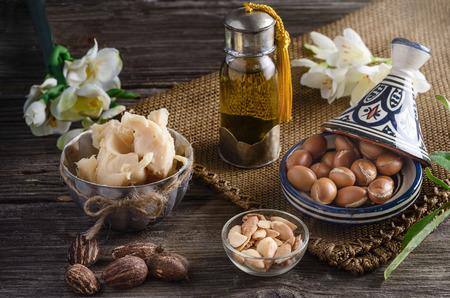 mantequilla: La naturaleza muerta de aceite de arg�n y frutas y la manteca de karit� con nueces en una mesa de madera con flores