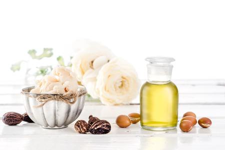 huile: Nature morte de fruits et huile d'argan et le beurre de karit� avec des noix sur une table en bois avec des fleurs Banque d'images