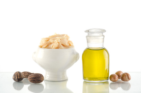 Still life of argan oil and shea butter with fruit and nuts