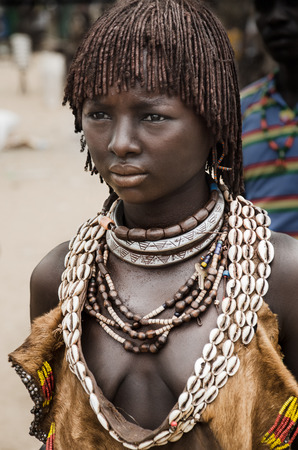 ethiopian ethnicity: Turmi, Ethiopia, August 11: Unidentified Hamer woman at the market in Turmi, Ethiopia, 11 August 2014. The two metallic necklace means she is a seconf wife Editorial