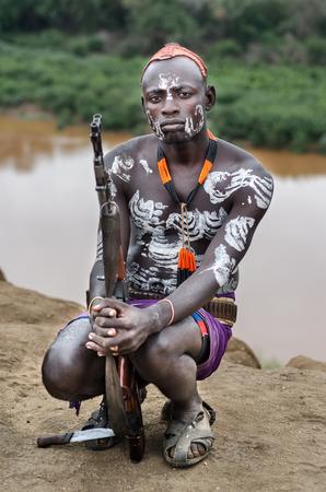 body painting: TURMI, ETHIOPIA - 12 AUGUST: unidentified man from Karo tribe in his village near Omo River, Ethiopia, on august 12, 2014. Karo tribes are famous for their body painting