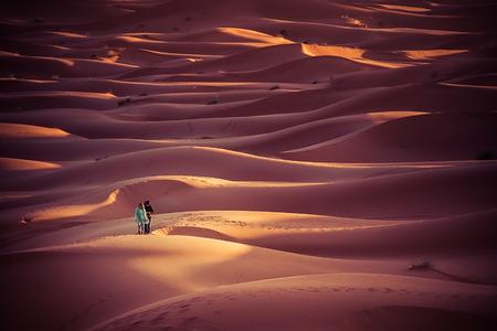 desierto del sahara: Merzouga Marruecos 27 de marzo de 2015: personas no identificadas caminar en las dunas del desierto del Sahara al amanecer. Pasar una noche en el desierto y mirar el amanecer es uno de los principales actration de Marruecos Editorial