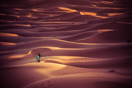 desierto del sahara: Merzouga Morocco  27 March 2015: unidentified people walk in the dunes of the Sahara desert at sunrise. Spend a night in the desert and look at the sunrise is one of the main actration of Morocco Editorial