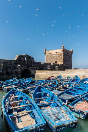 fortification: Blue boats in the harbour of Essaouira and the tower of the fortification walls Editorial