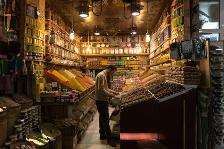 spice market: MARRAKECH, MOROCCO - 30 MARCH 2015: unidentified man sells dried fruits and spice in his shop in the old suk of Marrakech