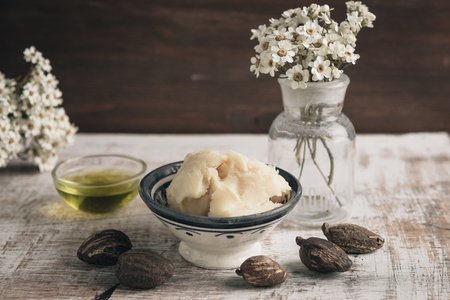 Two bowl of shea butter and oil with shea nuts on shabby wooden table.