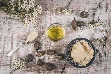 mantequilla: La manteca de karité y aceite de karité con frutos secos sobre una mesa blanca con la flor blanca en mal estado y la cuchara de plata