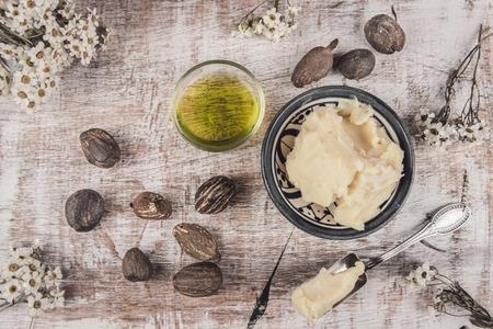 Shea boter en olie met shea noten op een sjofele witte tafel met witte bloem en zilveren lepel