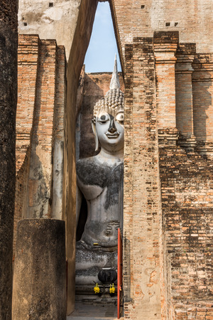 chum: Sukhothai historical Park, entrance of Wat Si Chum with the giant statue of Buddha