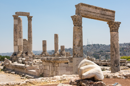 roman pillar: Ancient ruins of a roman temple in the Citadel of Amman. The hand of a statue in the foreground