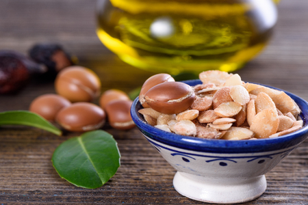 Close up of Argan fruits and oil with leaves Stock Photo