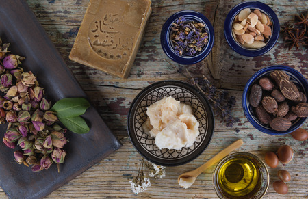 Mix of herbs, flower, argan nut and oil, shea nuts and butter, anise and Aleppo soap on wooden table