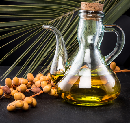 palm fruits: Bottle of palm oil and palm fruits on black background Stock Photo