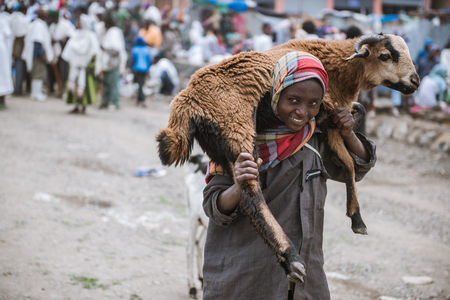 sold small: SIMIEN MOUNTAINS, ETHIOPIA - AUGUST 29,2015: crowded weekly market in a small village in Ethiopia. In these markets are sold of kind of goods and animals