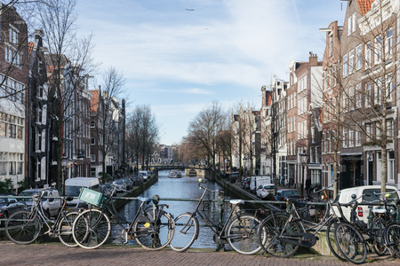 make public: AMSTERDAM, THE NETHERLANDS - 20 JANUARY, 2017: Bycicles parking on a canal. Public transports are expensive and that make bycicles the main means of transport in Amsterdam Editorial