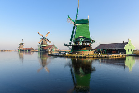 Old wind mills in Zaan Scans, near Amsterdam, in winter, with the iced water in the river Stock Photo