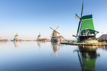 water mill: Old wind mills in Zaan Scans, near Amsterdam, in winter, with the iced water in the river Stock Photo