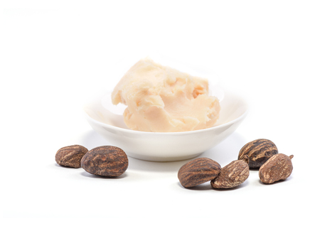 mantequilla: Shea butter nuts on white and a bowl of shea butter, close up