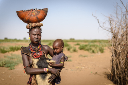 animal woman: OMORATE, ETHIOPIA - AUGUST 17, 2015: unidentified Dassanech woman with her child, wearing an animal leather and a decorated container on her head Editorial