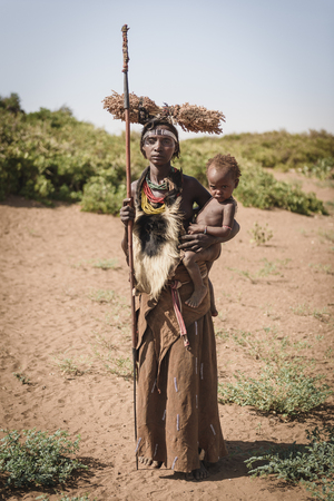 animal woman: OMORATE, ETHIOPIA - AUGUST 17, 2015: unidentified Dassanech woman with her child wearing an animal leather. She has a lance in her hand and carries branches on the head