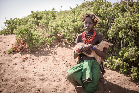 baby goat: OMORATE, ETHIOPIA - AUGUST 17, 2015: unidentified girl from Dassanech tribe hold a little goat. She wear a beautiful hat made of beer caps