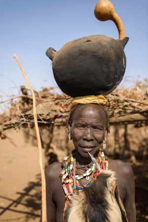 ornated: OMORATE, ETHIOPIA - AUGUST 17, 2015: unidentified Dassanech woman carries a big vase on her head with a lance in a hand. She is richly ornated and wear an animal leather Editorial