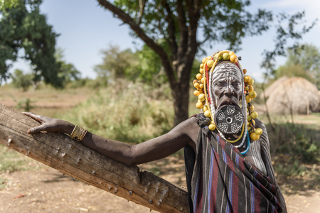 MAGO NATIONAL PARK, ETHIOPIA - AUGUST 19, 2015:  unidentified old Mursi woman with big lip plate and beautiful fruit decoration on her head. Lip plate is an old tradition of Mursi that is now disappearing in new generations