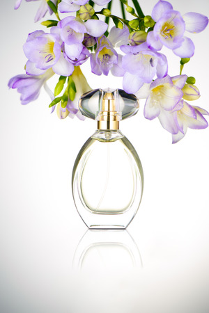 Bottle of perfume with flowers on glass table