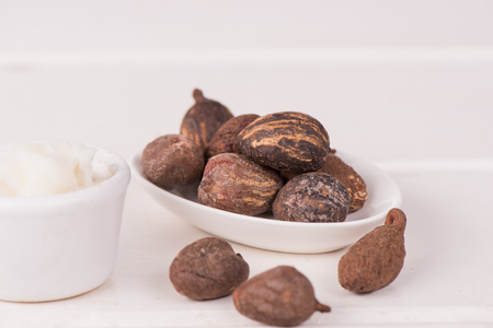 Shea butter nuts on white table with a cup of shea butter, Close ip.